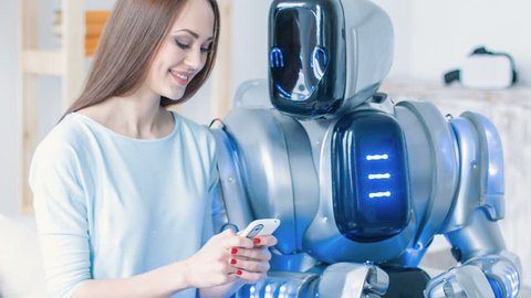 Nice cheerful woman sitting on the couch with robot