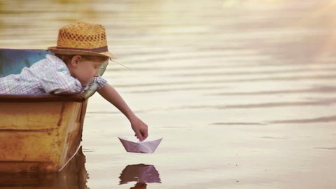 Boy places a paper boat on the water's surface and blows for it to sail away