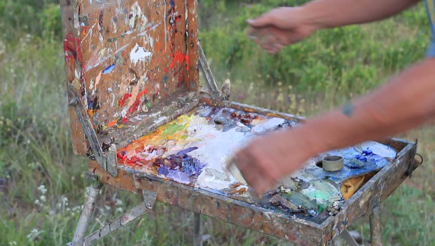 Portable easel, with telescopic legs and built-in paint box and palette. Closing the box | Shutterstock HD Video #17437855