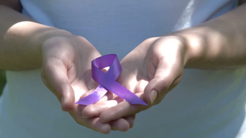 Close-up shot of woman hands holding purple ribbon in sunlight. ADD, ADHD, domestic violence, Alzheimer disease, pancreatic cancer | Shutterstock HD Video #17512285