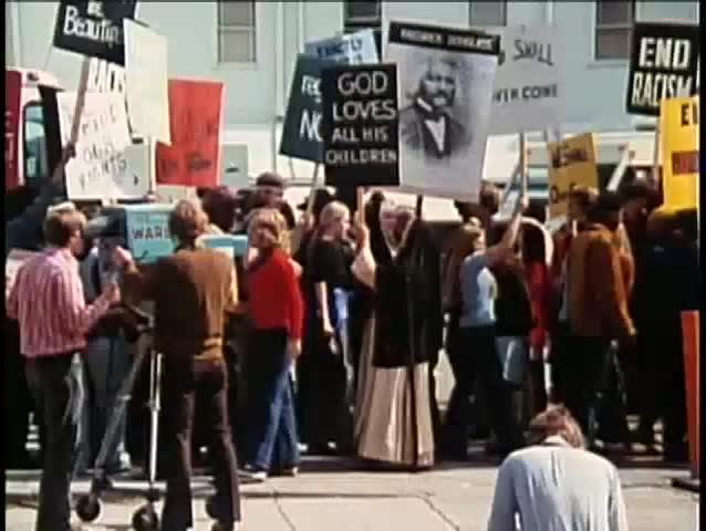 Demonstrators holding signs during protest, 1970s