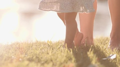 Little baby learns to walk. First Steps. Slow Motion 120 fps, 4K. Mother is teaching her child to do the first steps on a green grass in summer. Close up on feet. Happy childhood and Maternity. Family