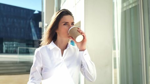 Attractive young businesswoman wearing modern suit and drinking coffee to go at break outdoors, working at modern business center,  slow motion