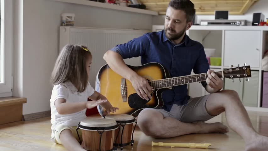 Father and daughter playing musical instruments, sitting on floor