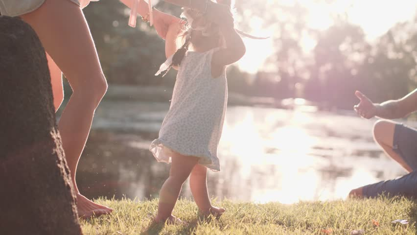 Little baby learns to walk. First Steps. Slow Motion 120 fps, 4K. Parents are teaching their child to do the first steps on a green grass in summer. Happy childhood and Parenthood concept. Family love | Shutterstock Video #17554444