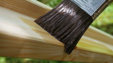 4K footage. Close-up paintbrush varnishing wooden plank