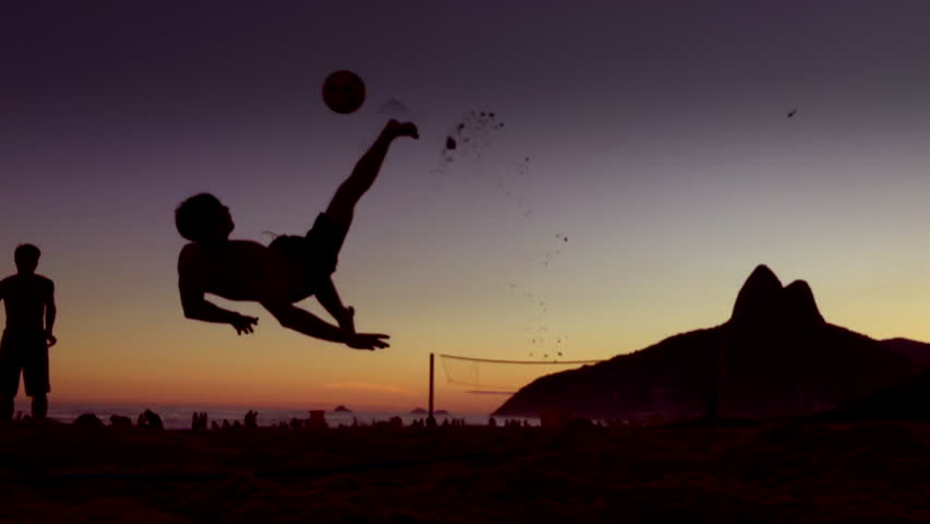 Defocus silhouettes of Brazilians playing footvolley in slow motion against a dark sunset backdrop of Two Brothers Mountain on Ipanema Beach, Rio de Janeiro Brazil