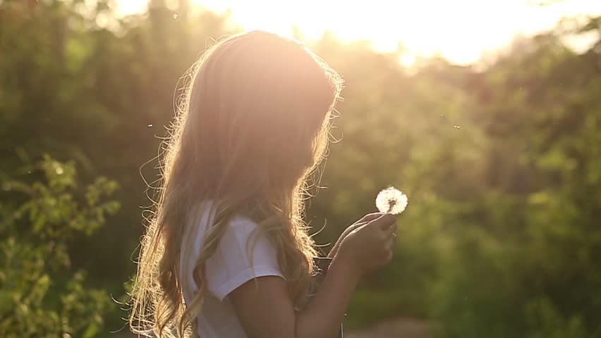Little cute girl blow a dandelion. Rest at nature. Slow motion