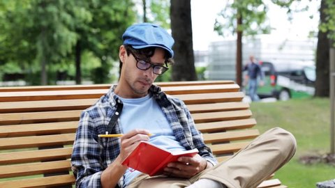 lifestyle, creativity, art, inspiration and people concept - creative man or artist with pencil and sketchbook erasing his drawing something sitting on city street bench