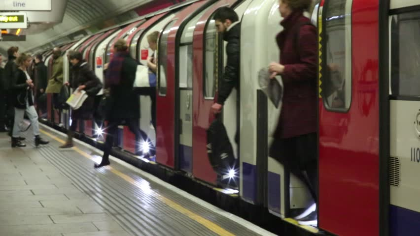 London, UK, 2016. London's tube network is over crowded and in need of repair. In this shot the train doors open and hundreds of people pile onto the platform on their way to work.