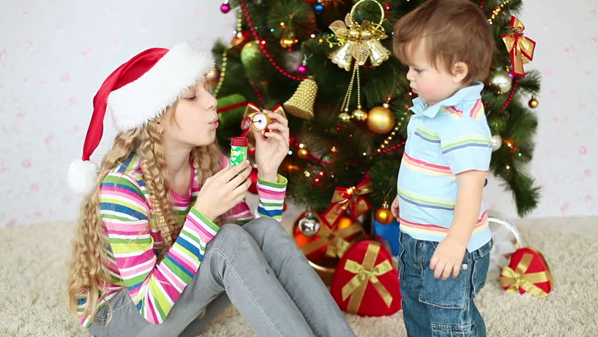 Sister and brother near the Christmas tree. Girl blowing bubbles