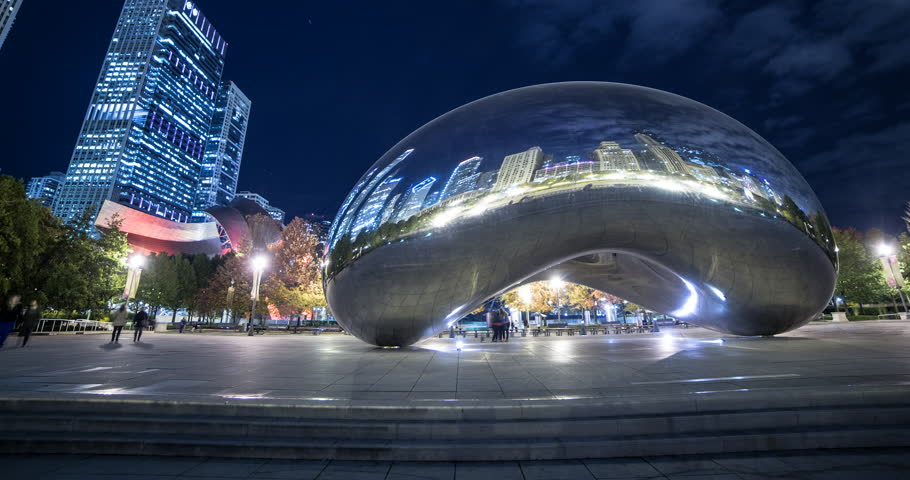 "Chicago, Illinois, USA - view of Cloud Gate ""the bean"" with reflections of illuminated skyline at Millennium Park at night with a few clouds - Timelapse with motion and zoom out"