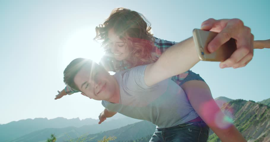 young family having fun resting and taking a selfie portrait on the background mountains sunset time,slow motion