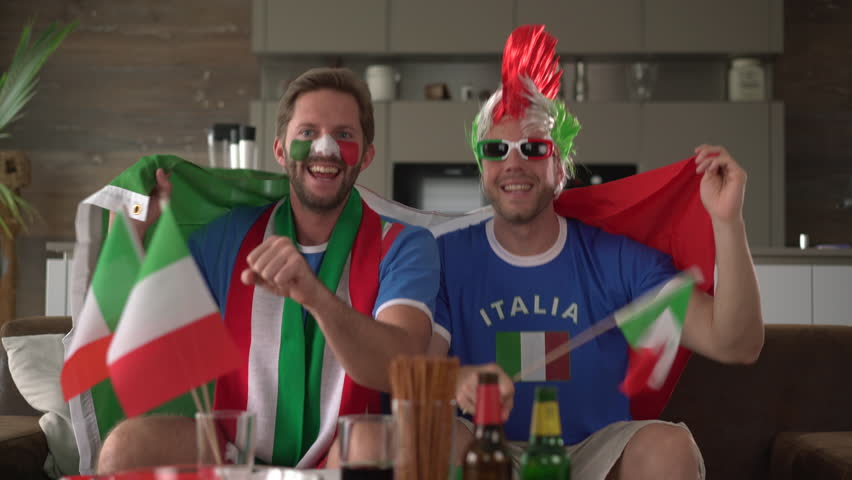 4K footage, two happy mates with italian t shirts and flag cheering for Italy in front of tv at home