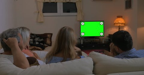 Back view of a family with child, parents and grandparents sitting on the sofa at home and watching TV in the evening. Chroma key with tracking motion markers