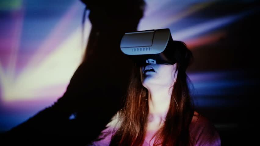 Woman using VR-helmet in the spotlight