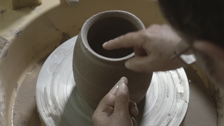 Pot maker using his hands makes pottery,at small home workshop,slomo 50p.Slow motion clip of a mature adult traditional pot maker hand crafting pottery and decorations with old/traditional tools.