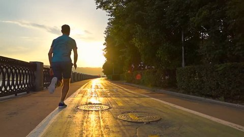 Man in blue uniform running on summer sunset embankment along bicycle road, Moscow. Super slow motion steadicam shot at 240 fps