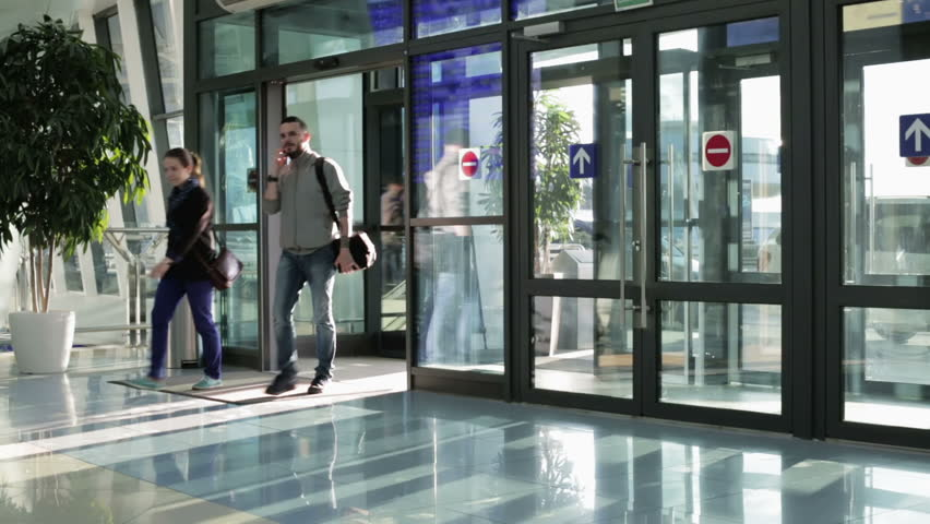 Man and woman come in the sliding door of the airport a guy with a man and woman come in the sliding door of the airport a guy with a bag on his shoulder passes into the glass building girl travels with a boyfriend planetlyrics Choice Image
