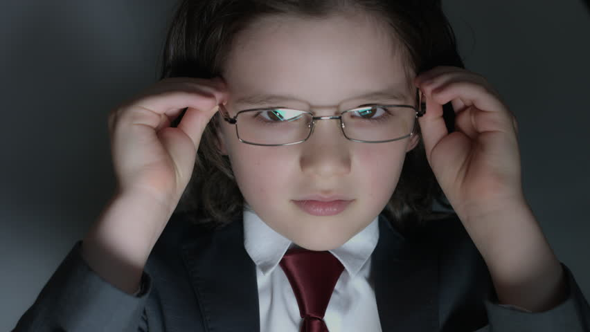 eyeglasses fashion dw86  4k shoot of a cute child posing as a business man in studio putting glasses