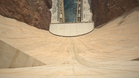 View from Over the Edge of the Hoover Dam. camera moves over the edge of the Hoover Dam Wall looking down, then tilts up to show the memorial bridge
