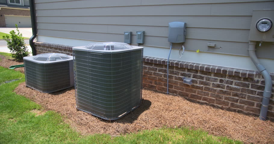 Two Central Air Conditioning Units Angled Rise Up. camera rises on a set of central air conditioning units on the side of a home. The electric meter is on the right side of the shot.