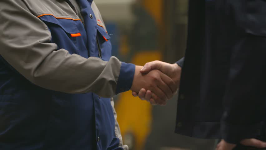 Two workers shake hands at the factory