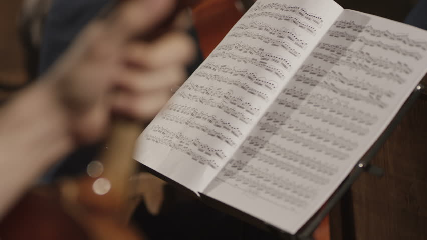 Hand, opening musical note paper sheet. Shot on RED EPIC Cinema Camera in slow motion.