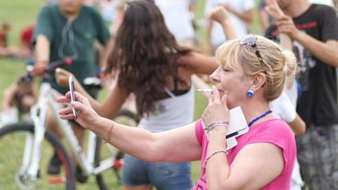 SOFIA, BULGARIA - JUN 27, 2016: Free music family festival in a park. Old age senior woman smoke cigarette shooting video via smart phone of concert