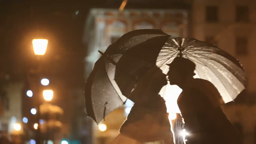 Romantic noir-styled couple under rain kissing on night city street, hiding from rain under umbrellas. City lights show pair silhouettes