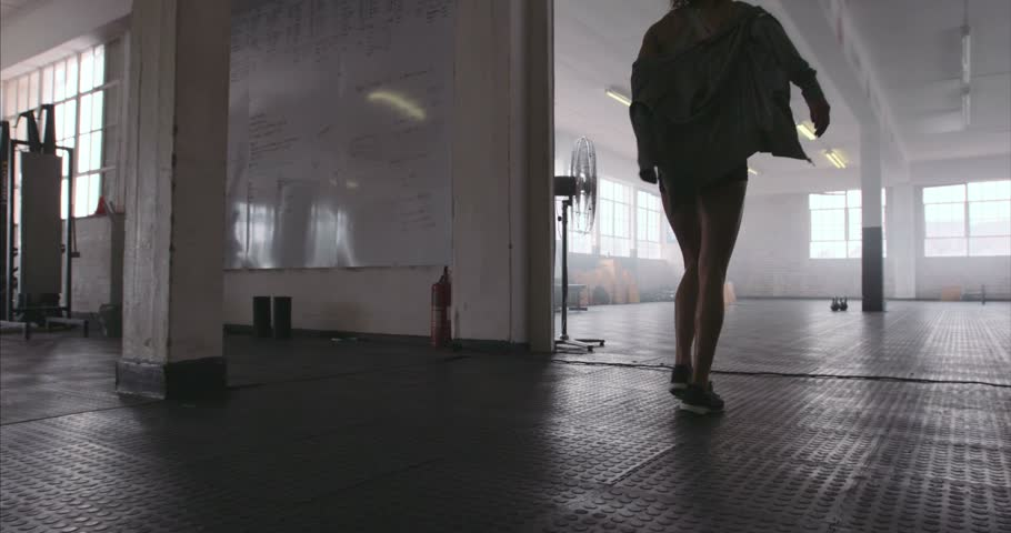 Fitness woman entering the gym, taking out her sweatshirt and picking up the kettle bell. Female athlete about the start her physical training at cross fit gym.
