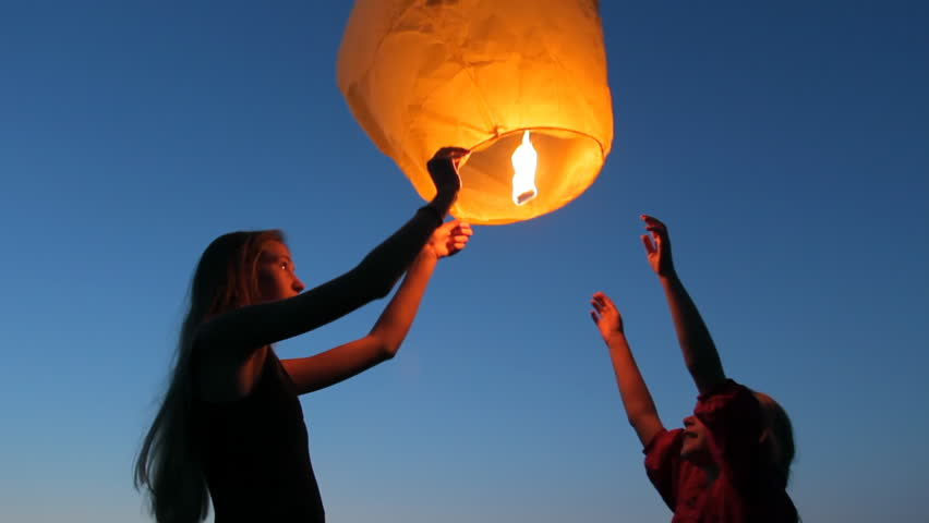Two young girls launching a Chinese sky fly fire lantern to make a wish, summer holidays, celebration, family, children