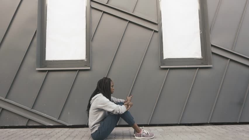 Young african american woman looking sad and choose music to listen on her phone. Grey wall background | Shutterstock HD Video #17880418