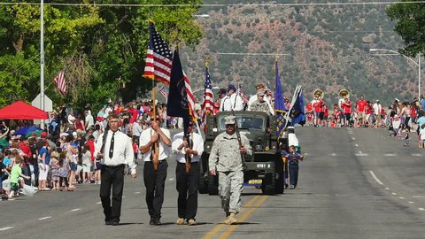 MORONI, UTAH - JULY 4, 2016: Color guard marches with US flag and Utah state flag to mark the start of annual 4th of July parade in a small rural American town as they celebrate America's independence