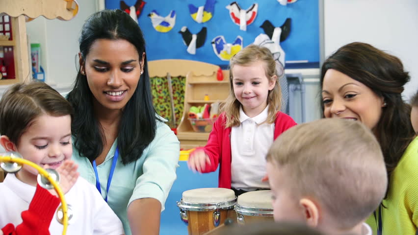 Nursery students enjoying a music lesson in the classroom with their teachers.