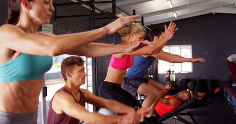 Group of people performing plyometrics exercise in gym 4k