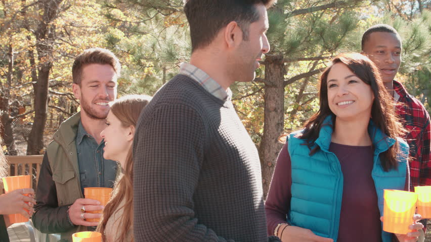 Friends stand talking at a barbecue, one grilling, close up | Shutterstock HD Video #17945275