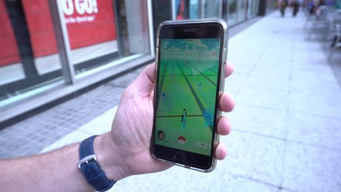 New York City, NY - July 2016: Pokemon Go app being played by a man on his iphone while walking down a manhattan street.  Location based mobile game created by Nintendo uses GPS and camera to interact