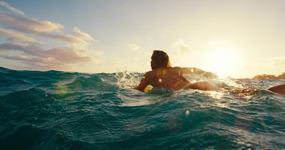 Surfer paddling over blue ocean wave at sunset in slow motion, outdoor fitness lifestyle #17997595