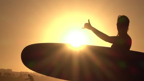 SLOW MOTION CLOSE UP SILHOUETTE: Cheerful young surfer female showing shaka sign over the golden setting sun. Surf girl with surfboard at beach in summer evening, beautiful orange sunset in background