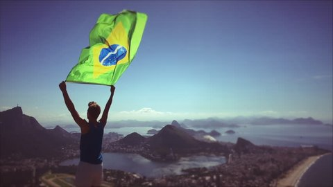 Athlete stands holding a Brazilian flag waving in slow motion at a bright overlook of the city skyline of Rio de Janeiro, Brazil
