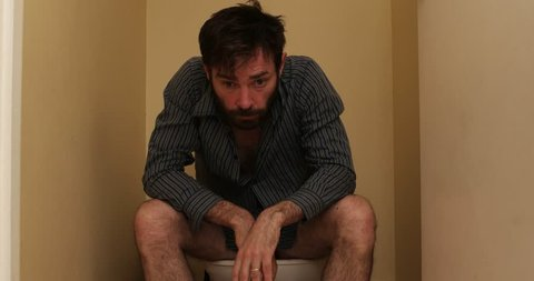 man on toilet suffering smell