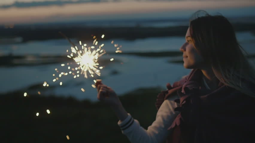 Beautiful young woman stands on a high hill with sparkler at sunset in slow motion