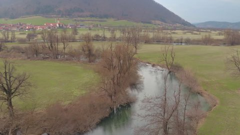 AERIAL: River meanders trough big valley with small town in background in late cloudy autumn