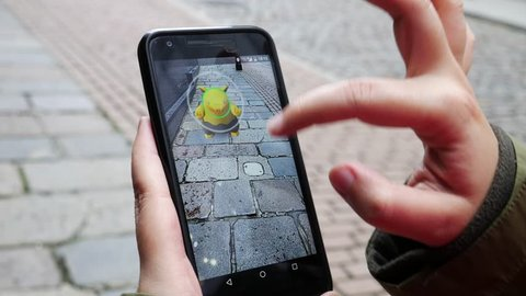 """ABERDEEN, UNITED KINGDOM - JULY 15, 2016: People playing """"Pokemon GO"""" the hit augmented reality smart phone app while trying to find Pokemon on July 15, 2016 in Aberdeen, United Kingdom."""