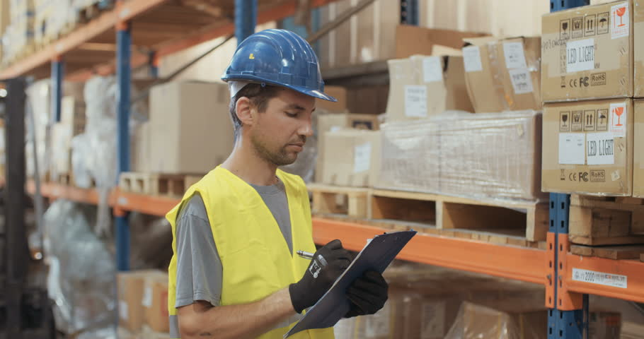 Warehouse worker uses a tablet writes data on the availability of logistics worker with a helmet inspecting items in a warehouse using a clipboard 4k stock sciox Choice Image