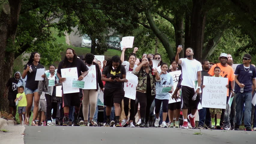 Shelby, North Carolina: July 16, 2016.  Protesters march with signs and fists raised during a Black Lives Matter protest
