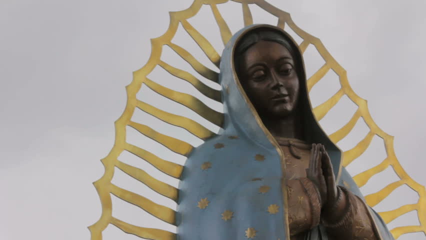 Closeup of of a statue of the Virgin of Guadalupe. The low angle of the religious icon symbolizes an imposing feeling. Dark clouds gather ominously behind the beautiful Mexican Catholic saint.