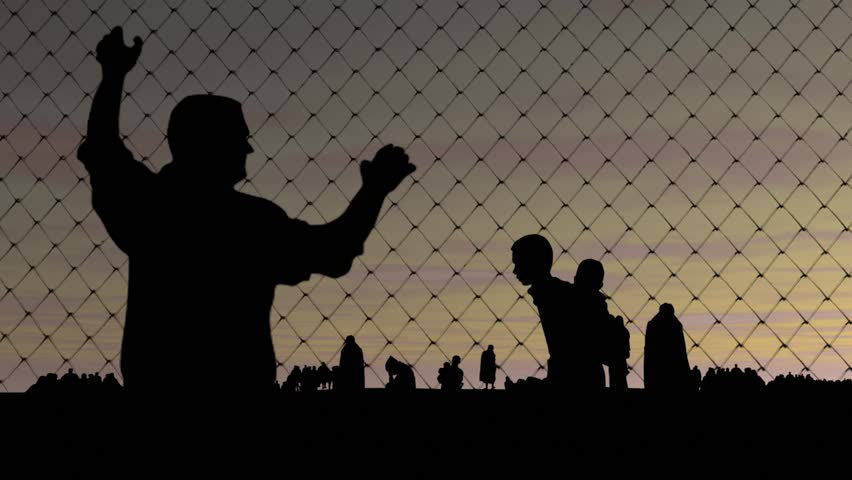 Refugees. Migrants behind barbed wire.