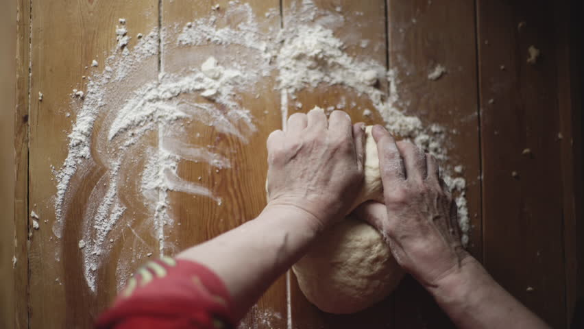 Old woman grandmother is kneading dough on a wooden table. 4K